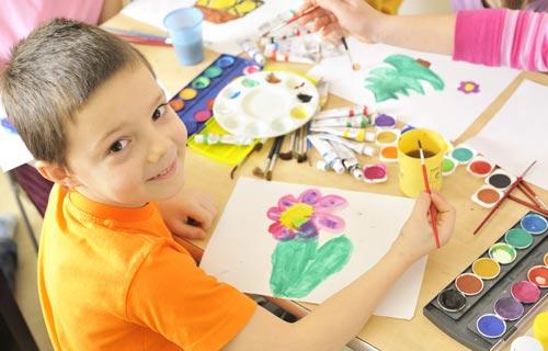 niño colorea naturaleza con pintura en una mesa